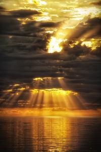 Light punches through a storm cloud after a rain